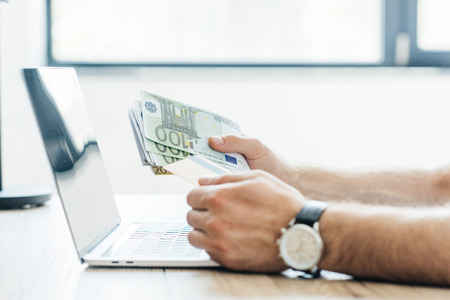 partial view of person holding credit card and euro banknotes at workplace