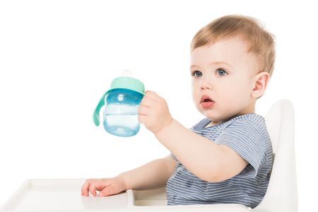 adorable little boy holding baby cup with water and sitting in highchair isolated on white background Stock Photo