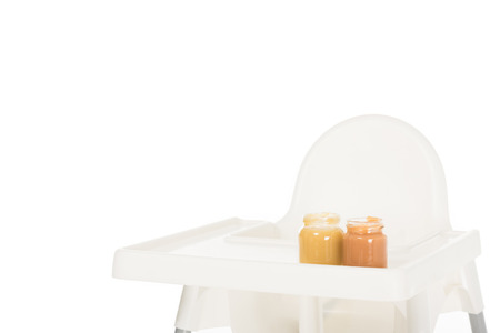 closeup shot of two jars with child puree on highchair isolated on white background Stock Photo - 106610802