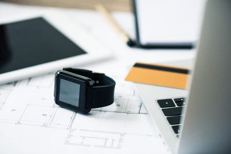 close-up view of smartwatch, laptop, digital tablet and blueprint at workplace