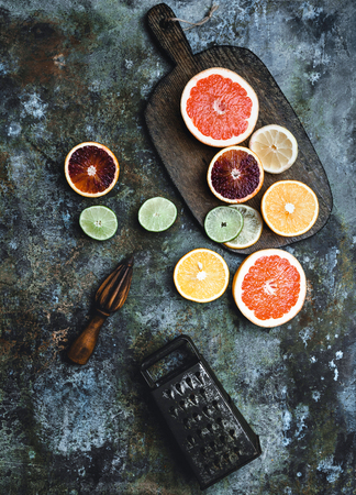 wooden squeezer, grater, cutting board and slices of grapefruit, lime, blood orange and lemon on tabletop