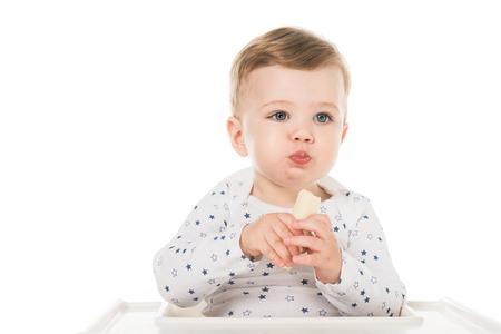 adorable little boy eating banana isolated on white background