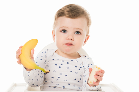 little boy with bananas sitting in highchair isolated on white background Stock Photo