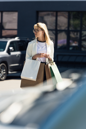 selective focus of young blonde woman with shopping bags walking on parking lot