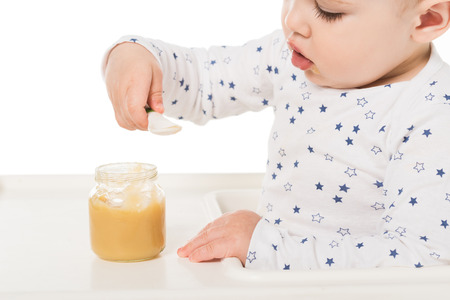 baby boy eating puree from jar and sitting in highchair isolated on white background Stock Photo