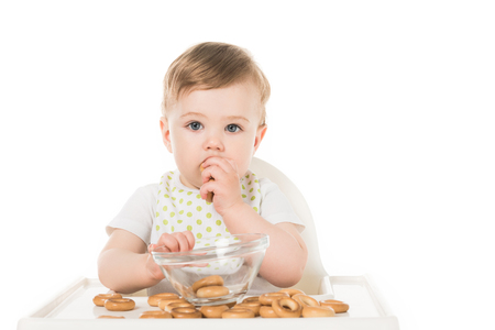 adorable baby boy eating bagels in highchair isolated on white background Stock Photo - 106610762