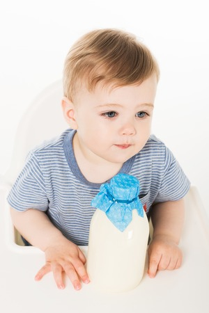 high angle view of little boy with bottle of milk and sitting in highchair isolated on white background Stock Photo - 106610768