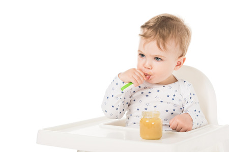 child eating puree from jar and sitting in highchair isolated on white background Stock Photo