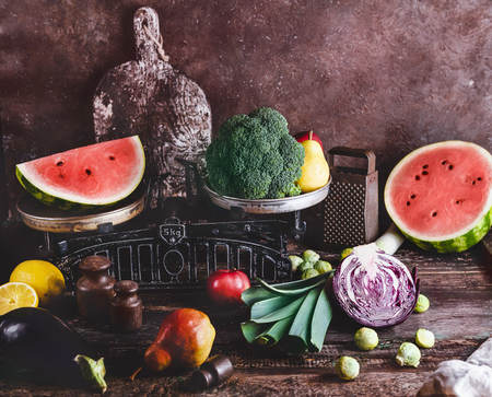 closeup shot of scales, grater, cutting board, different fruits and vegetables on rustic wooden tabletop