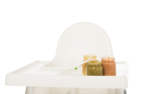 closeup view of three jars with child puree and spoon on highchair isolated on white background Stock Photo