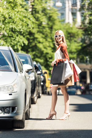 full length view of stylish young woman with paper bags standing near car on street