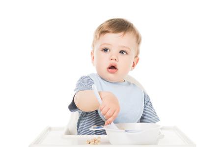 Adorable petit garçon en bavoir assis en chaise haute et manger à la cuillère isolé sur fond blanc