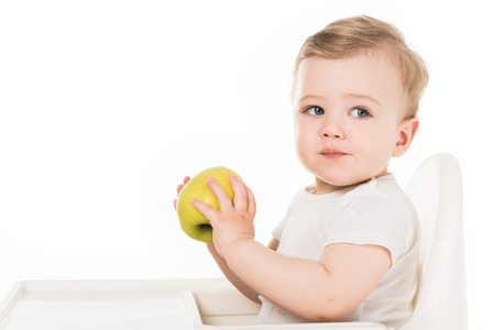 baby boy eating apple and sitting in highchair isolated on white background 스톡 콘텐츠