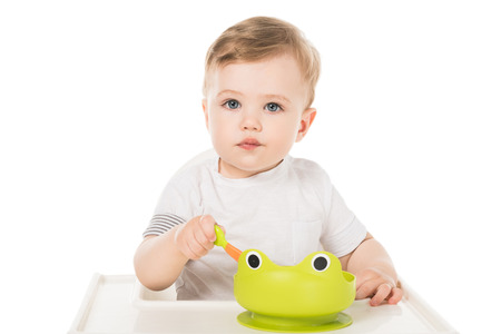 adorable little boy eating from plate in form of frog and sitting in highchair Stock Photo