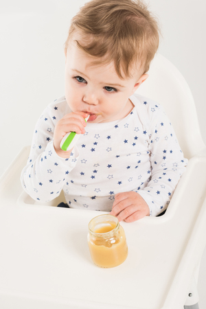 high angle view of baby boy eating puree from jar and sitting in highchair isolated on white background Stock Photo