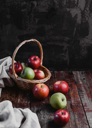 kitchen towel, wicker basket and apples on rustic wooden table