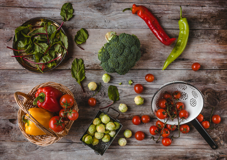 top view of wicker basket, plate, colander, cherry tomatoes, peppers, mangold leaves, broccoli and brussel sprouts
