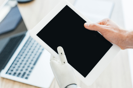 close-up view of human hand and robotic arm holding digital tablet with blank screen