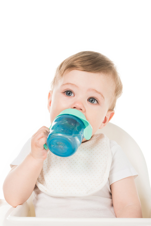 little boy drinking water from baby cup in highchair isolated on white background