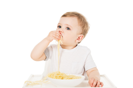 little boy in highchair eating spaghetti by hand isolated on white background Stock Photo - 106561473