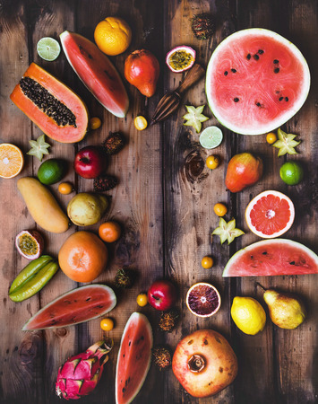 elevated view of wooden squeezer and pile of different fruits on wooden table
