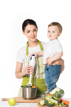 mother holding hand blender and son standing on table with ingredients isolated on white background