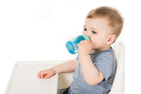 little boy drinking water from baby cup and sitting in highchair isolated on white background Archivio Fotografico