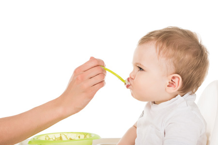 cropped image of mother feeding adorable little son in highchair isolated on white background