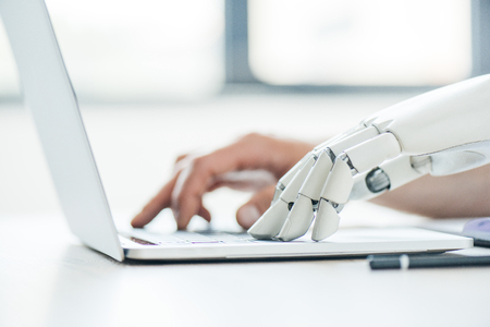 selective focus of human and robot hands typing on laptop at workplace 免版税图像