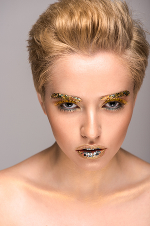 beautiful woman with golden glitter on face looking at camera isolated on grey Stock Photo