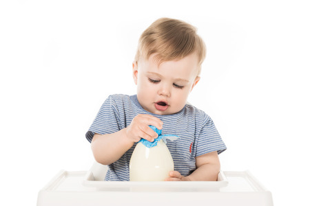 little boy trying to open bottle of milk and sitting in highchair isolated on white background