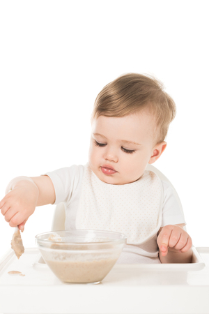 baby boy eating porridge by spoon and sitting in highchair isolated on white background Stock Photo - 106561222