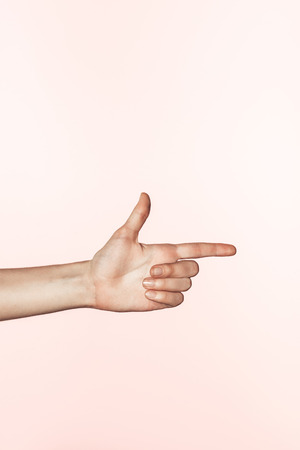 cropped image of woman pointing by finger isolated on pink background