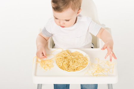 high angle view of baby boy sitting in highchair and eating spaghetti by hands Stock Photo - 106560863