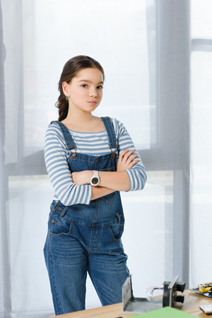 preteen child standing with crossed arms and looking at camera at home