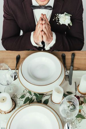 cropped shot of groom in suit praying while sitting at served table, rustic wedding concept Standard-Bild - 106557054