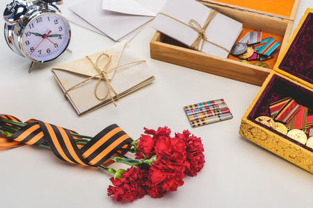 closeup shot of carnations wrapped by st. george ribbon, letters, medals in boxes and alarm clock, victory day concept Stock Photo - 106557068