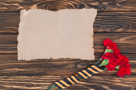 top view of empty old paper and carnations wrapped by st. george ribbon