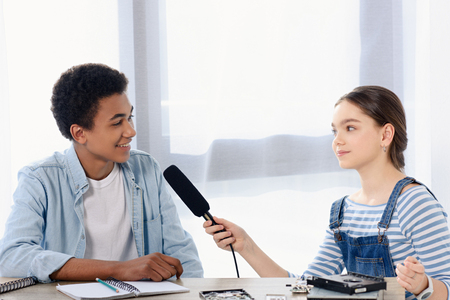 caucasian teen kid conducting interview with african american friend for vlog at home Stock fotó
