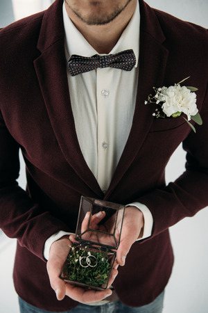 partial view of groom in suit with buttonhole and wedding rings in box in hands Standard-Bild - 106557123
