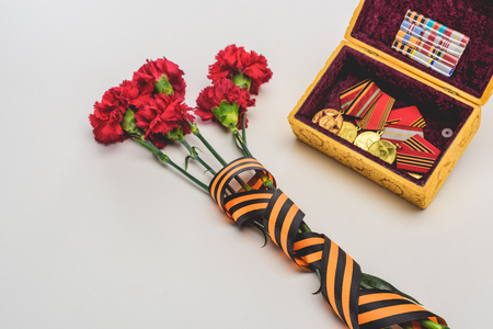closeup shot of flowers wrapped by st. george ribbon and box with medals, victory day concept