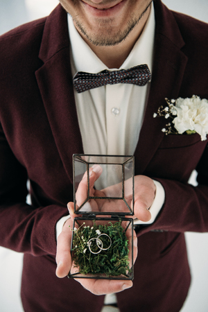 partial view of groom in suit with buttonhole and wedding rings in box in hands Standard-Bild - 106557357