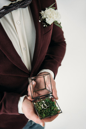 partial view of groom in suit with buttonhole and wedding rings in box in hands Standard-Bild - 106557367