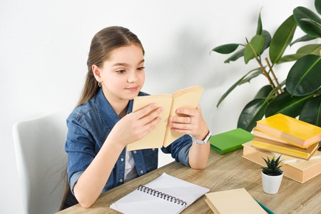 adorable preteen child reading book at home Stockfoto