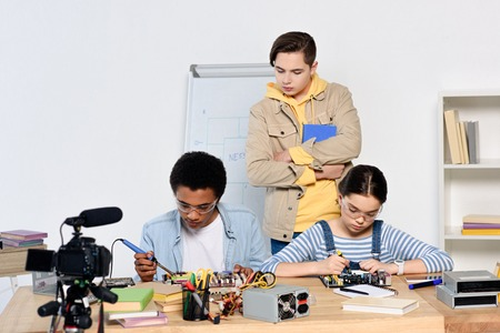 teen boy watching how multicultural friends soldering computer circuit with soldering iron at home Zdjęcie Seryjne