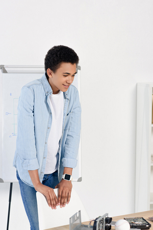 african american teenager looking at table with technical equipment at home Stock Photo