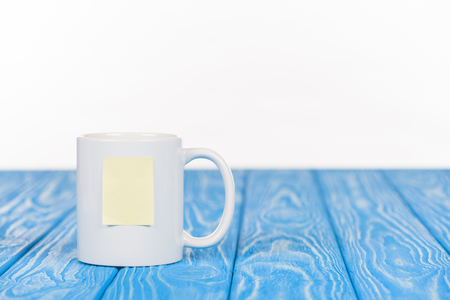 closeup shot of cup with empty note paper on wooden blue surface Stock Photo