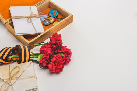 closeup shot of box with medals, stacks of letters, carnations wrapped by st. george ribbon on gray, victory day concept Stock Photo - 106557631
