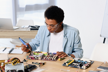 african american teenager soldering computer circuit with soldering iron at home Stock fotó