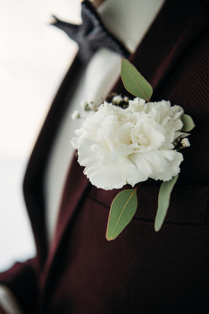 partial view of groom in suit with beautiful white corsage